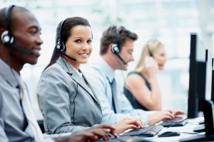 Attractive female working in a call center with her colleagues